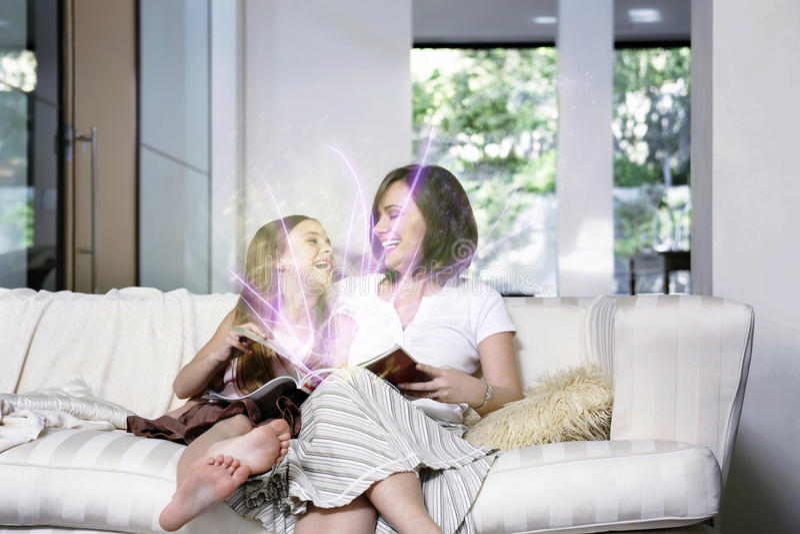 读不可思议的书的母亲和女儿在客厅 免版税库存图片