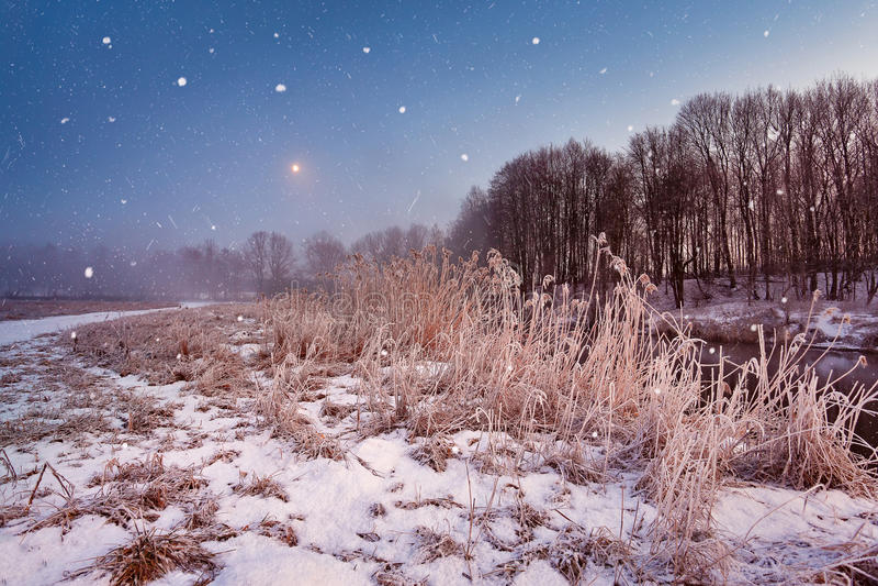 不可思议的冬天圣诞夜 在河的降雪场面 免版税图库摄影