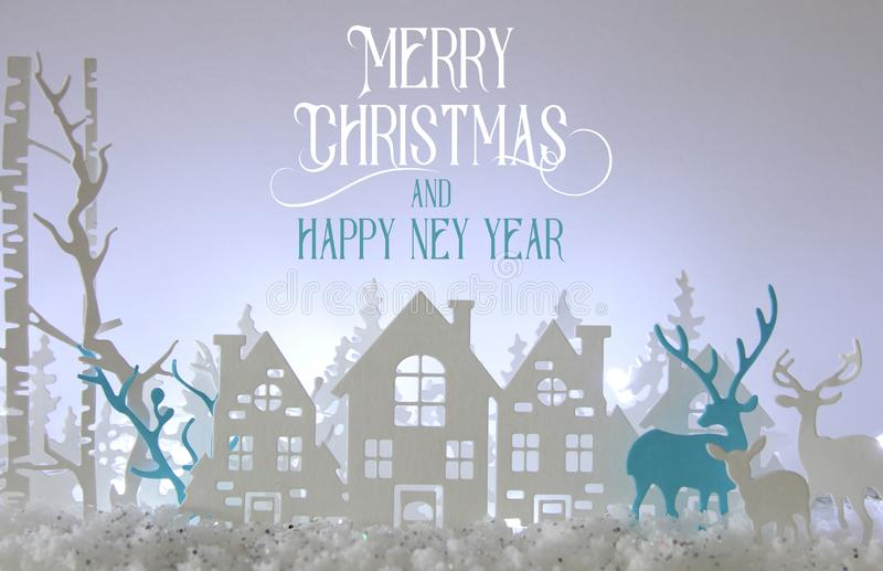 不可思议的圣诞节纸削减了冬天与房子、树、鹿和雪的背景风景在白光背景前面 免版税库存照片