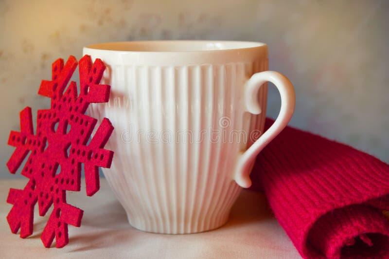 不可思议的圣诞节-白色杯子、红色雪花和被编织的围巾-舒适寒假时间 库存照片