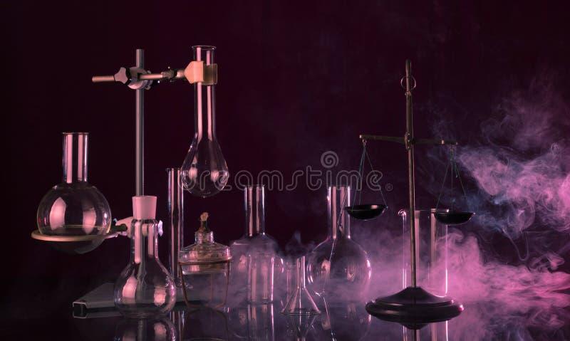 不可思议的实验室 化学对比标度,三脚架以盘品种在黑暗的背景的在红色烟 免版税库存图片