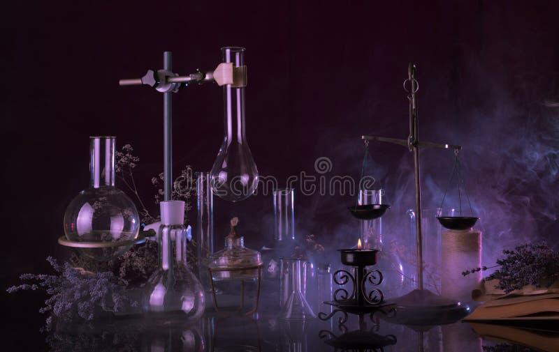 不可思议的庸医的医术仪式 玻璃烧瓶,点燃了一本蜡烛和古老书在神奇烟 库存图片