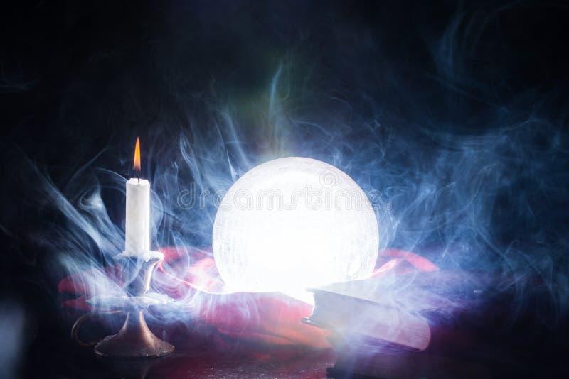 不可思议的水晶点燃在桌上的球与在烛台和书的蜡烛 免版税图库摄影