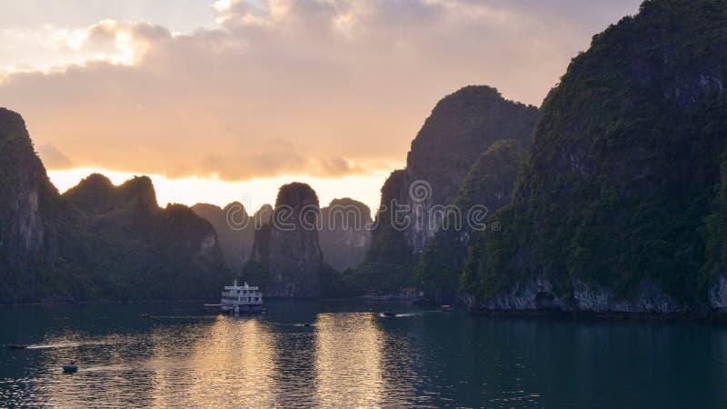 不可思议的金黄日落在下龙湾在越南,南海 巡航航行划线员船木破烂物航行岩石的海岛 免版税库存图片