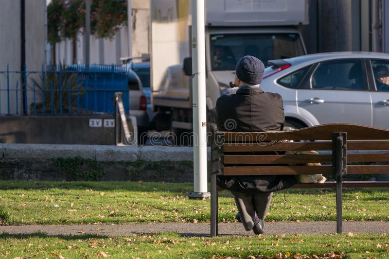 不可能验明的孤独的老人坐抽管子的公园长椅 免版税图库摄影