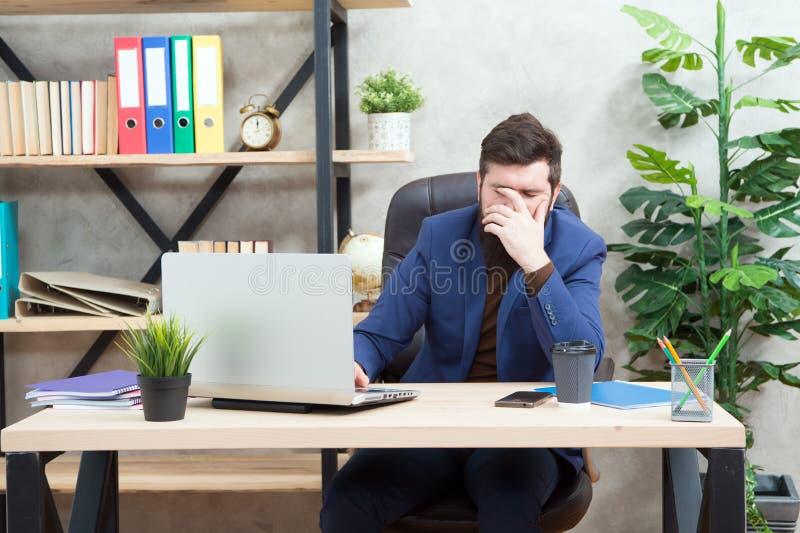 不合格的成交 下跌的股票行市 人有胡子的上司坐办公室膝上型计算机 在网上解决业务问题的经理 库存图片