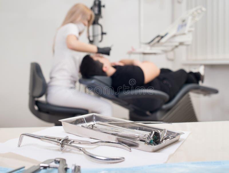 不同的专业牙齿仪器,在被弄脏的背景牙医治疗牙齿诊所的患者 免版税库存照片