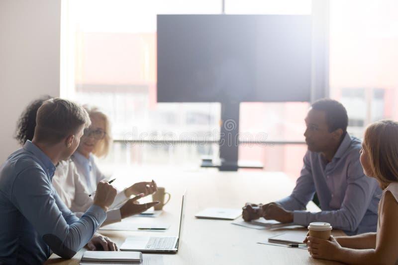 不同的买卖人小组坐在会议桌上在会议室里谈判 免版税库存图片