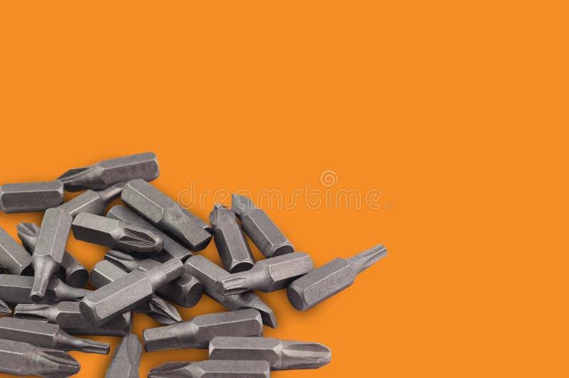 不同的互换性的头或位一堆手工螺丝刀的木材加工和金属工艺的在橙色背景w 免版税库存图片