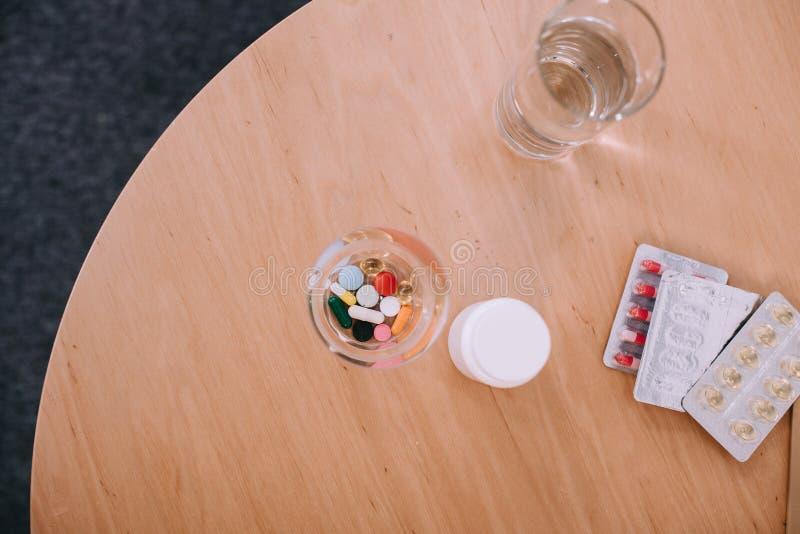 不同的五颜六色的药片和胶囊与杯水在桌上 库存照片