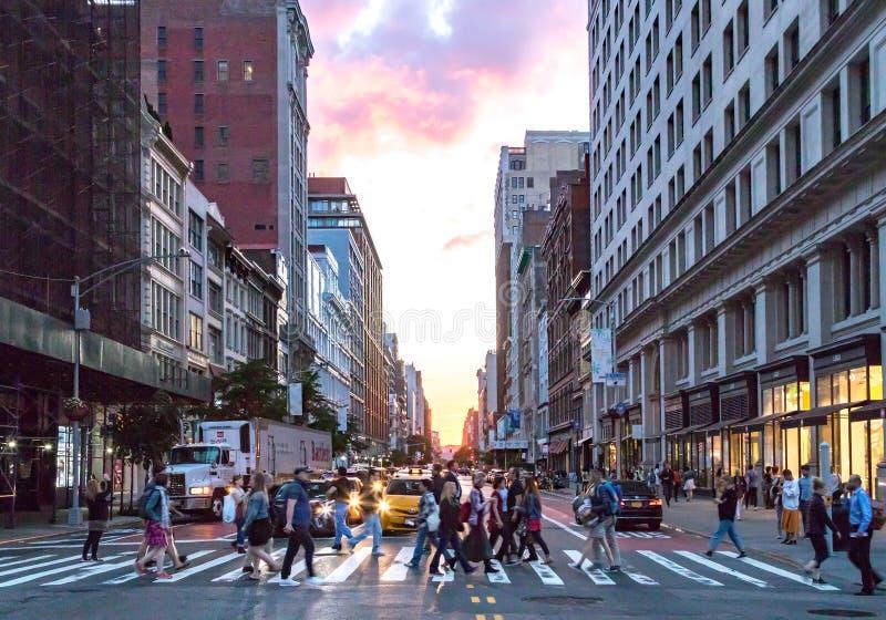 不同的人民人群在曼哈顿纽约穿过在第23条街道上的繁忙的交叉点和第5条大道 库存图片