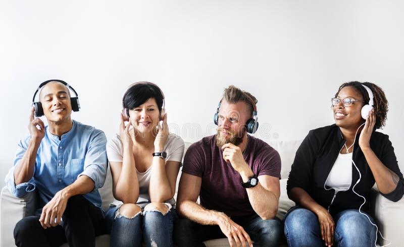 不同的人民坐长沙发佩带的耳机 免版税图库摄影