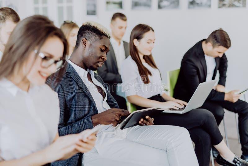 不同的办公室人民工作在手机的,拿着智能手机的公司雇员在见面 严肃多种族 库存图片