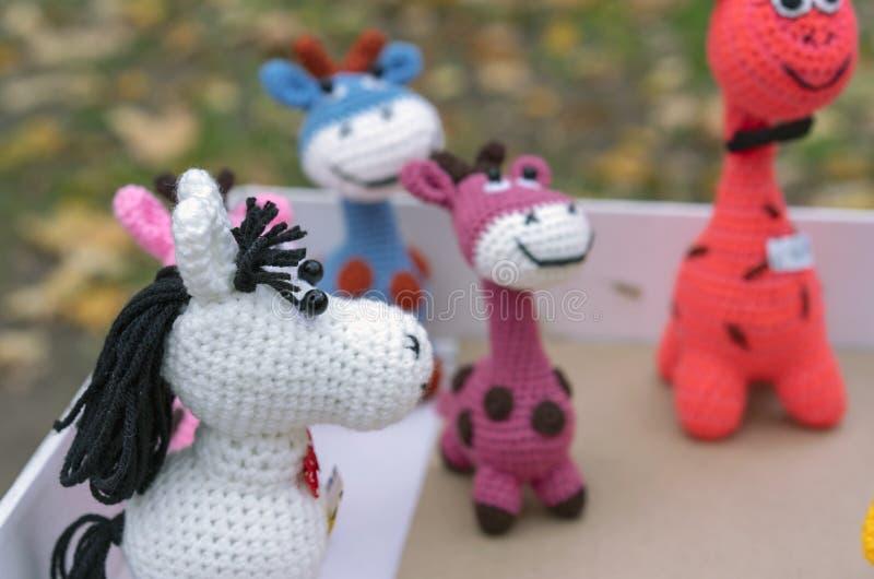 不同的动物被编织的五颜六色的玩具在街道礼品店的 库存图片