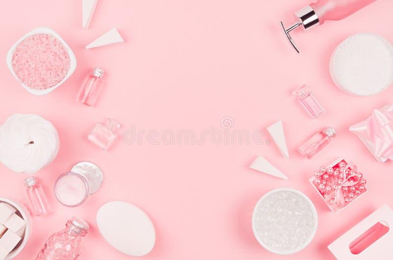 不同的化妆品和辅助部件在桃红色和银色颜色作为装饰边界在软的浅粉红色的背景 免版税库存照片