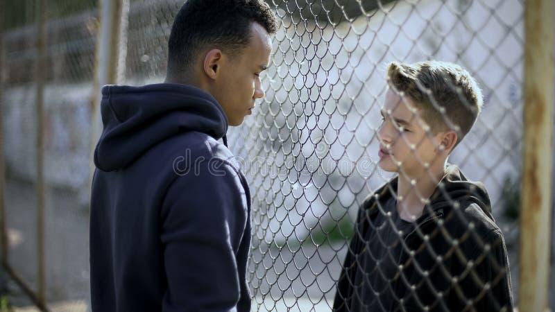 不同的国籍的两个男孩谈话,富有和贫寒由篱芭分离了 图库摄影
