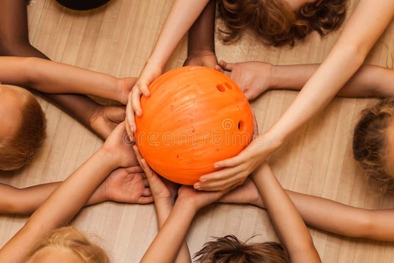 不同的国籍的儿童的手与一个保龄球的 图库摄影