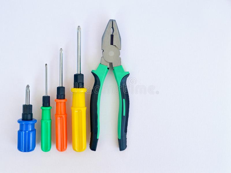 不同的大小四把螺丝刀与蓝色,绿色,红色和黄色把柄在木tablePliers和d四把螺丝刀的  库存照片