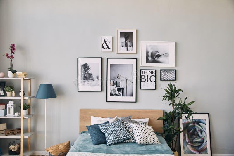 不同的大小照片在垂悬在床的框架的 卧室内部现代 免版税库存图片