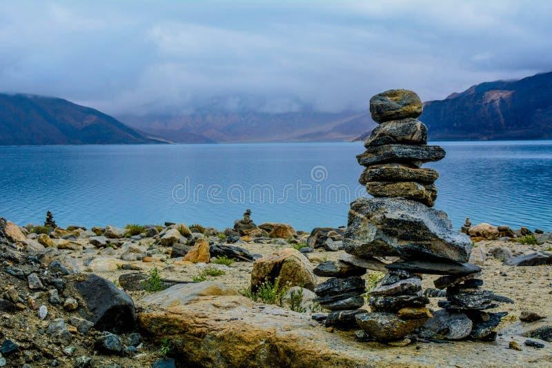 不同的大小的岩石被堆积和平衡的一个在别的在美丽的海的海岸 免版税库存照片