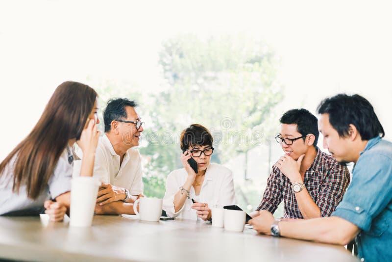 不同的小组五个亚洲人企业人在队会议在咖啡店或现代办公室 战略突发的灵感,小企业 库存照片