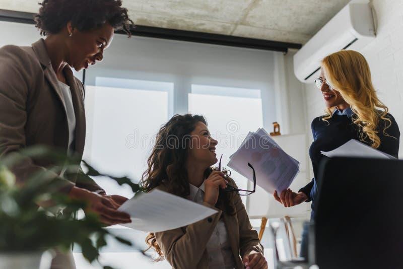 不同的小组微笑的女商人有断裂在办公室谈话 免版税库存图片