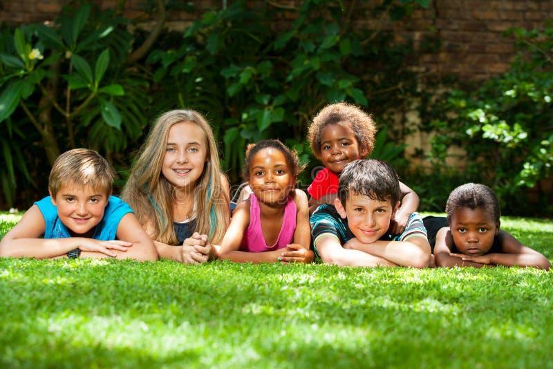 不同的小组一起孩子在庭院里。 免版税库存图片