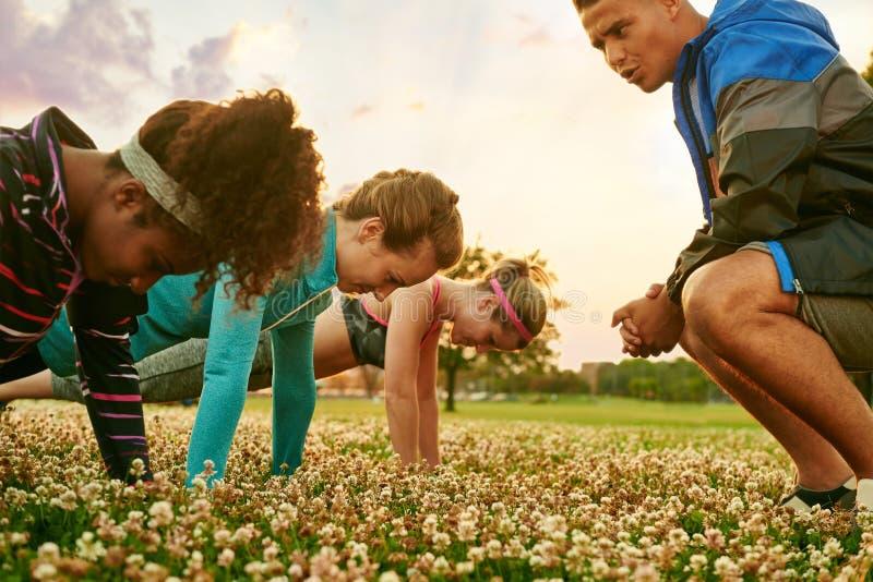 不同的小组在做俯卧撑的健身训练期间的妇女在日落在自然公园 免版税图库摄影