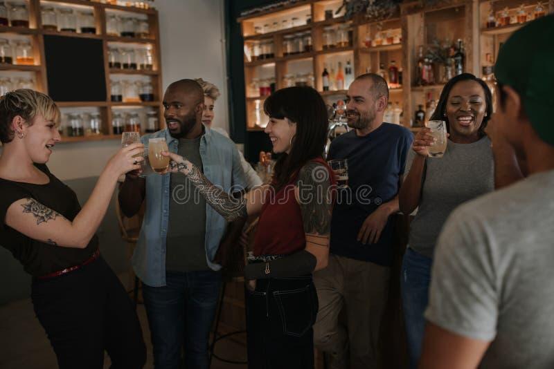 不同的年轻朋友获得乐趣一起在酒吧 库存照片