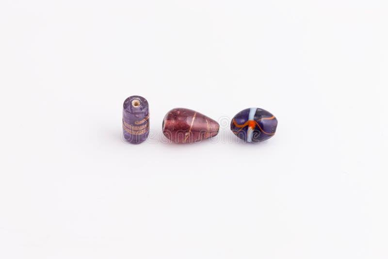 不同的形状三个紫色小珠和树荫做的 免版税库存照片