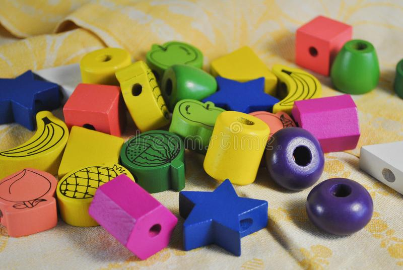 不同的形状木头明亮的色的小珠儿童的创造性的 星,苹果计算机,菠萝 免版税库存照片