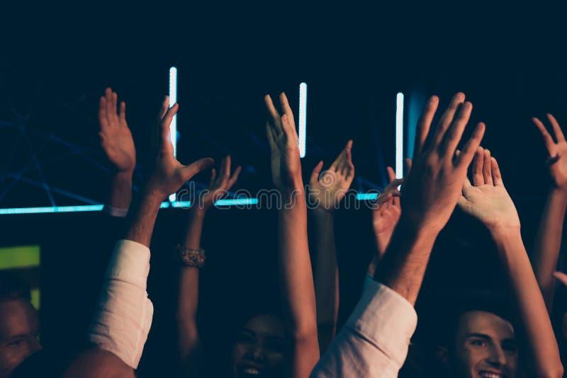 不同的快乐的朋友观众用在普遍的w的被举的手 免版税图库摄影