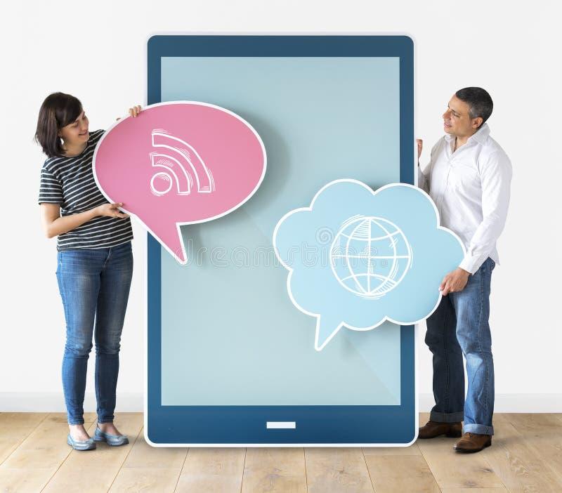 不同的拿着讲话泡影和片剂的人民拿着讲话泡影的和tabletCouple 图库摄影