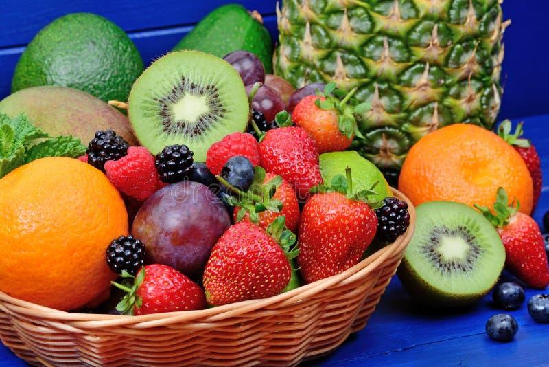 不同的果子和莓果堆在一个篮子在木桌上 免版税库存照片