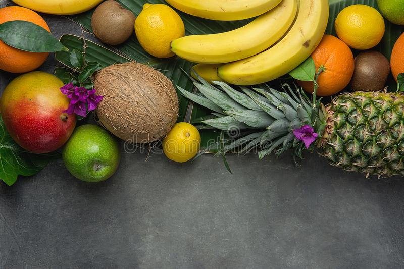 不同的热带夏天果子品种  菠萝芒果椰子柑橘桔子柠檬苹果在黑暗的石头的猕猴桃香蕉 库存照片