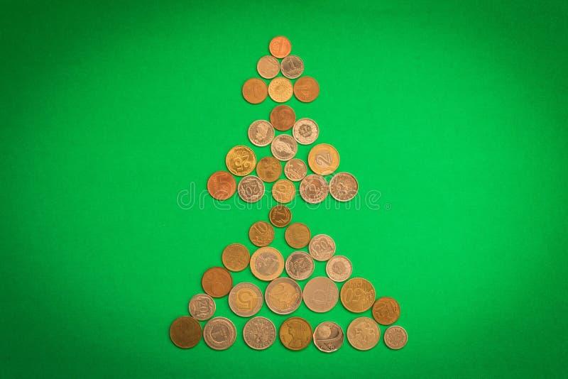 不同的硬币圣诞树在绿色背景的 圣诞节概念新年度 储款为假日 免版税图库摄影