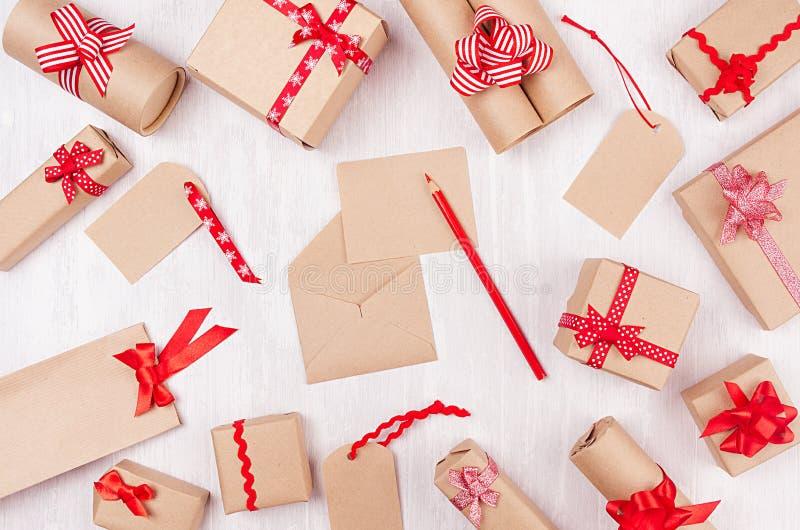 不同的礼物盒与红色弓和丝带的牛皮纸和与信封的空的信件在软的白色木背景 图库摄影