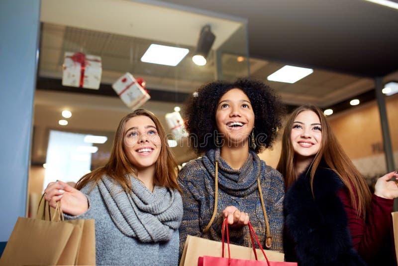 不同的种族的妇女与摆在在圣诞节新年销售的购物中心的购物带来的 画象三微笑 库存照片
