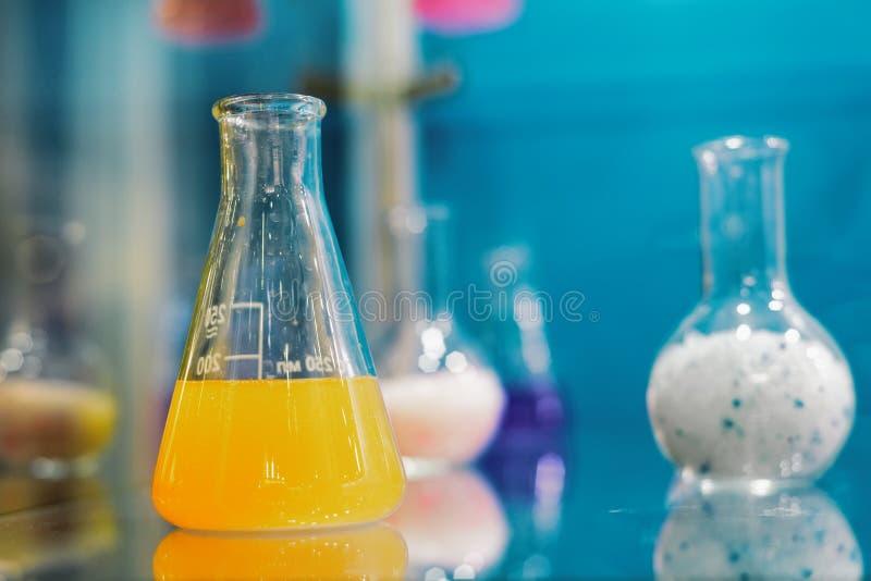 不同的粒子和液体在玻璃烧瓶 免版税库存图片