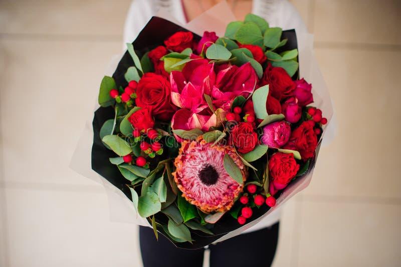 不同的红色花美丽的花束与黑纸的在手上 免版税库存照片