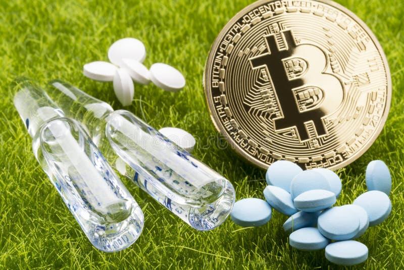 不同的药片和一次用量的针剂与bitcoin在草背景-医疗保健费用概念铸造 免版税库存照片