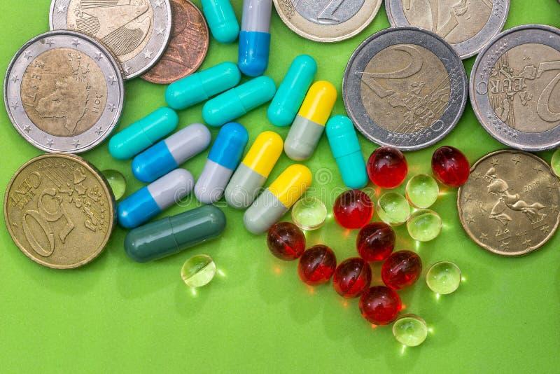 不同的药片和欧洲硬币在绿色背景 库存照片
