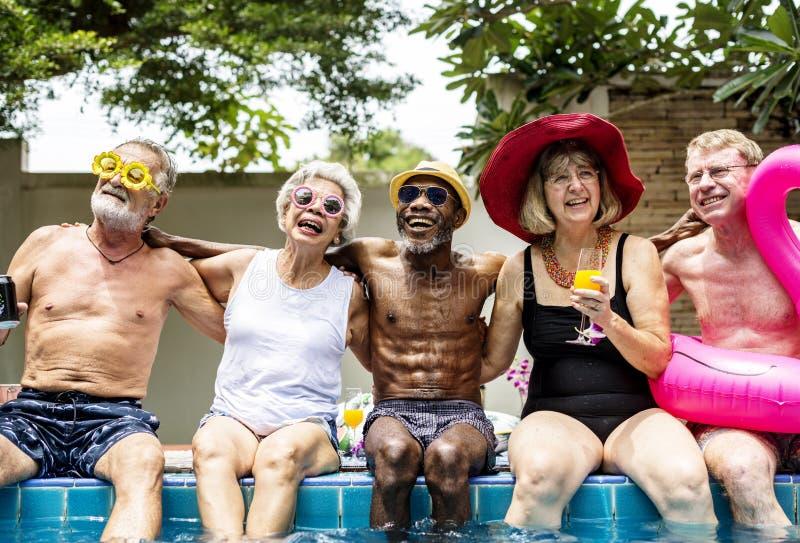 不同的资深成人坐由水池享受summ的小组 免版税库存照片