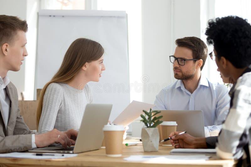 不同的雇员坐在遇见合作在办公室 图库摄影