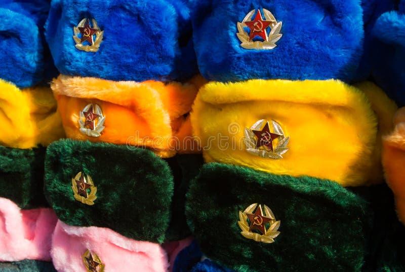 不同的颜色俄国冬天帽子行与军队象征的在老Arbat街道的街市上 免版税库存照片