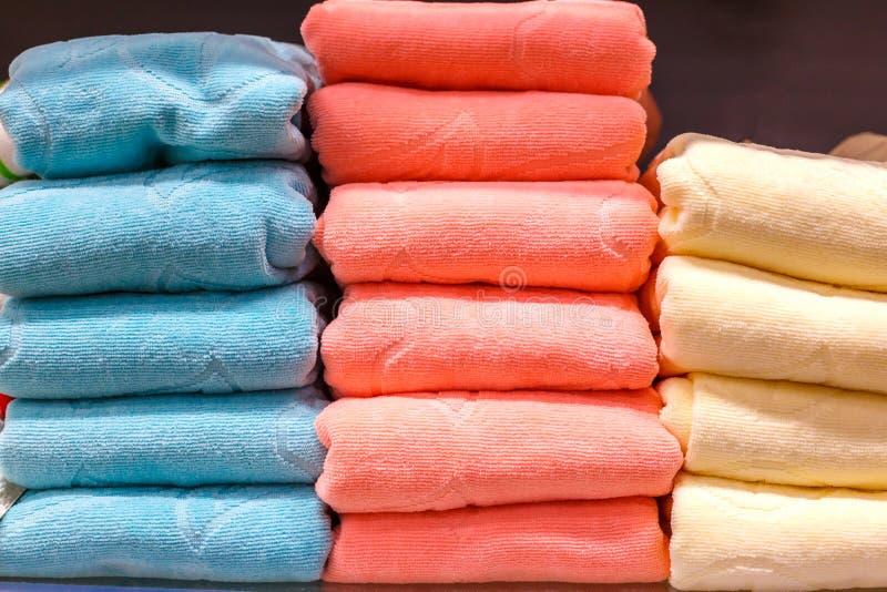 不同的颜色整洁地被折叠的毛巾在架子 免版税库存照片