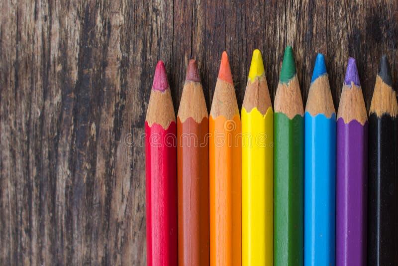 不同的颜色被削尖的石板笔在一张木桌上的 免版税库存照片