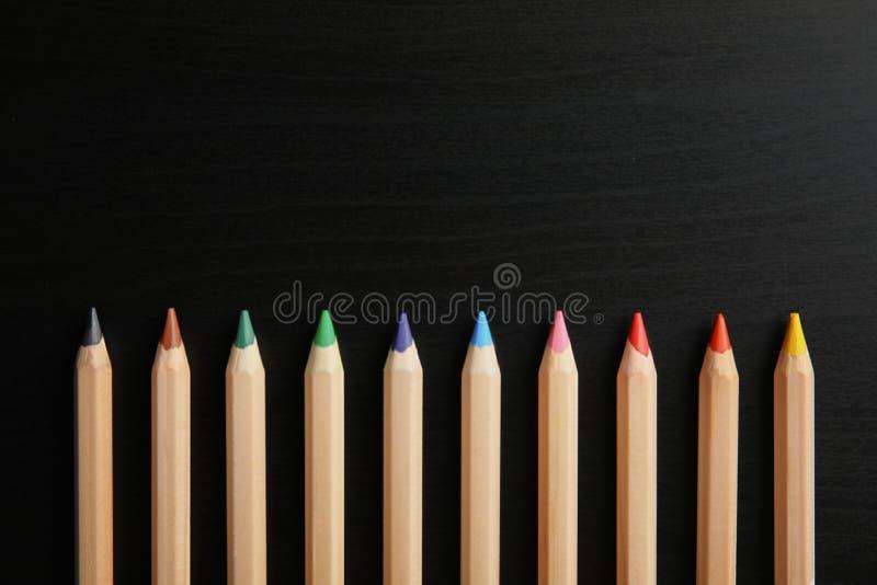 不同的颜色铅笔与空间的在木背景,顶视图的设计的 库存照片