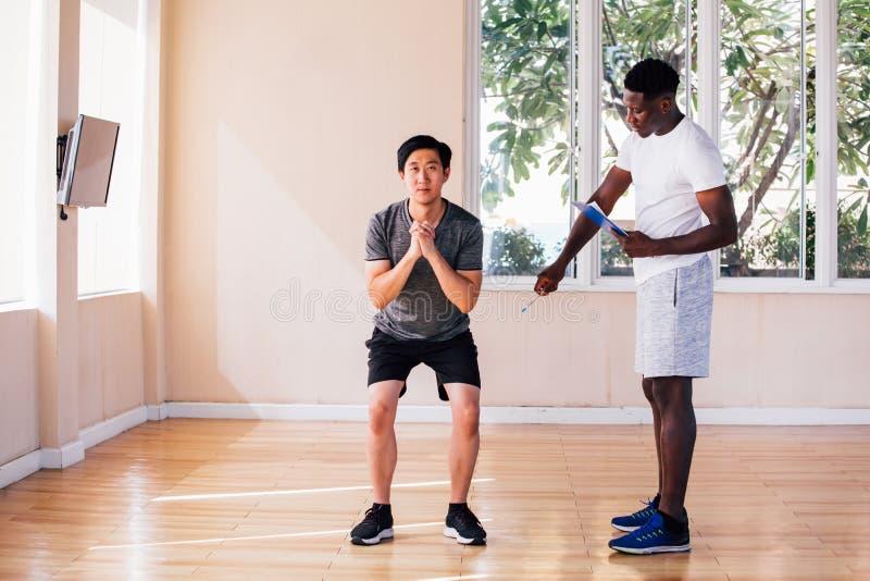 不同种族健身教练员和客户解决 图库摄影
