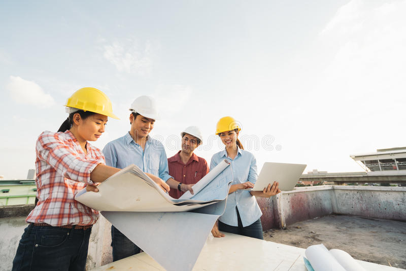 不同种族的不同的小组工程师或商务伙伴建造场所的,在building& x27; s图纸 库存照片